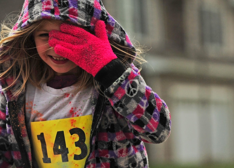A young runner wipes her eyes during the Minot Meltdown color run at Minot Air Force Base, N.D., April 25, 2017. Runners had the option of running a 5K or 10K race. (U.S. Air Force photo/Senior Airman Apryl Hall)