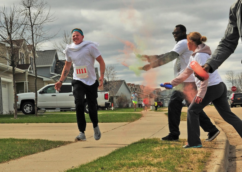 Volunteers throw color on a runner during the Minot Meltdown color run at Minot Air Force Base, N.D., April 25, 2017. There were six color stations throughout the race route. (U.S. Air Force photo/Senior Airman Apryl Hall)