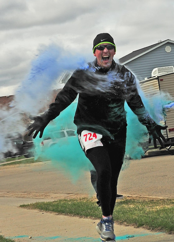 Tech. Sgt. Joshua Hull, 5th Maintenance Squadron crew chief, runs through a color station during the Minot Meltdown color run at Minot Air Force Base, N.D., April 25, 2017. This was the fourth annual color run hosted by the 5th Medical Group and Hull's fourth time participating in it. (U.S. Air Force photo/Senior Airman Apryl Hall)