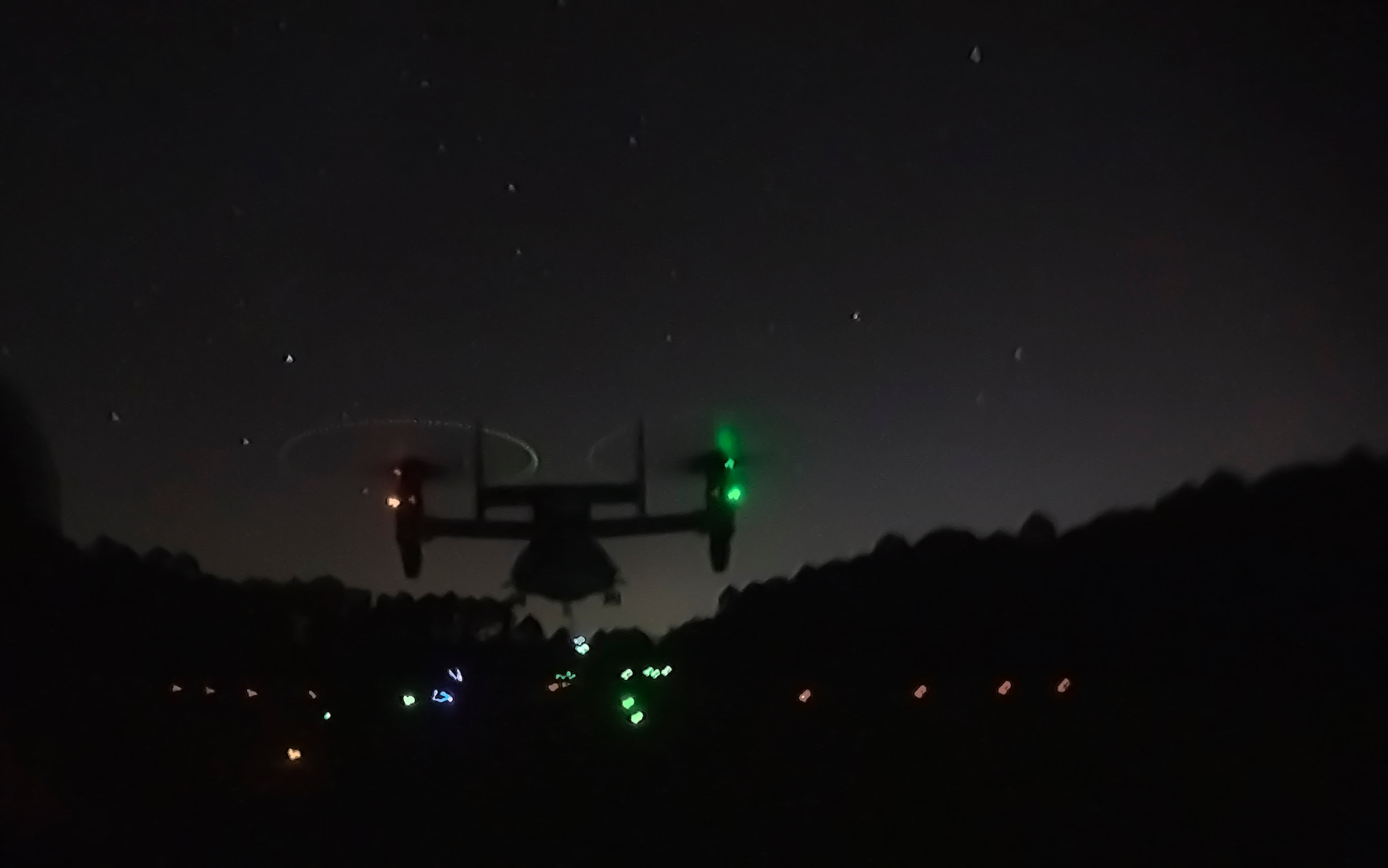 A MV-22B Osprey hovers over a landing zone while a helicopter support team attaches a load to the helicopter during an external lift exercise at Camp Lejeune, N.C., Jan. 24, 2017. External lifts provide a fast, effective way to move cargo and other heavy equipment, increasing the logistic capabilities of ground elements. The helicopter support team Marines are with Combat Logistics Battalion 26. (U.S. Marine Corps photo by Lance Cpl. Damarko Bones)