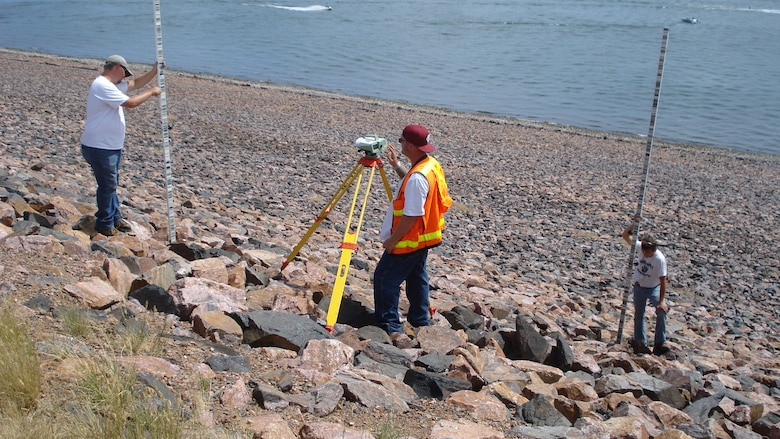 Field surveyors Nick Michael, Dave Salter and Michael Swinford run a level loop to establish current year elevations for tiltmeters, sensitive inclinometers designed to measure small structure changes, at Cherry Creek Dam near Denver, Colorado.