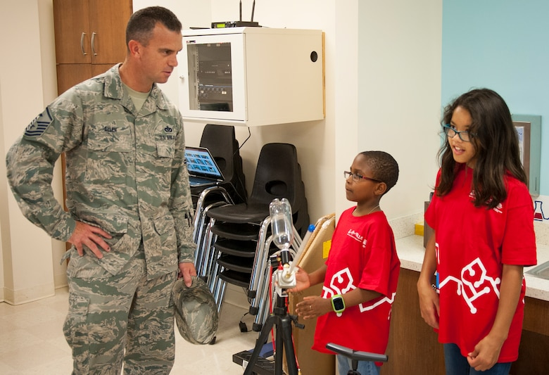 Master. Sgt. Jeffrey Allen, 96th Force Support Squadron first sergeant, and youth center members test new science equipment in the youth center's Center of Innovation April 20, 2017. (U.S. Air Force photo/Sara Francis)