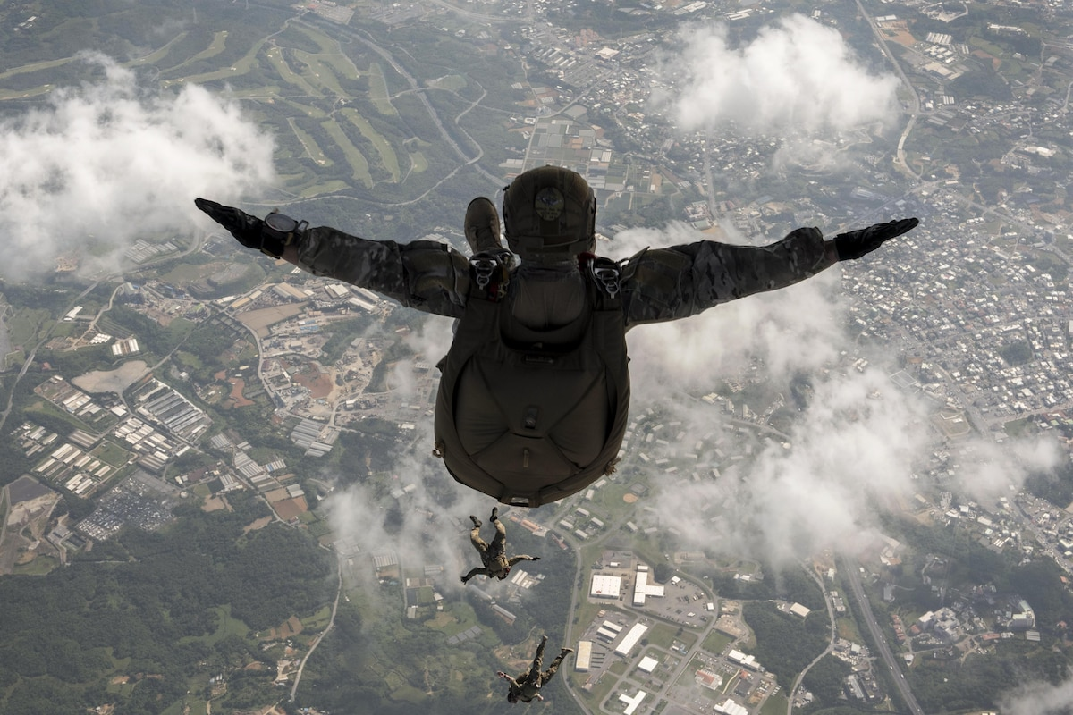 An airman spreads his arms as he jumps from an aircraft.