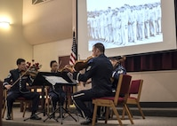 U.S. Air Force Band String members play while a slideshow of pictures are displayed during the Holocaust Commemoration at Joint Base Andrews, Md., April 26, 2017. The memorial featured an invocation, prayers and a speech made by Dr. Alfred Münzer, Holocaust survivor. (U.S. Air Force photo by Senior Airman Jordyn Fetter)