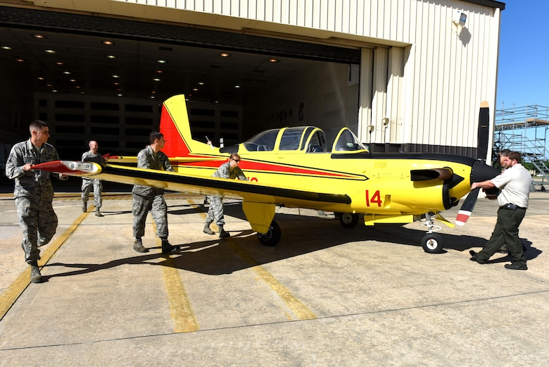 Members from the 4th Equipment Maintenance Squadron corrosion control shop guide a freshly painted North Carolina Forest Service T-34C Turbo Mentor aircraft out of the 4th Equipment Maintenance Squadron corrosion control shop, April 26, 2017, at Seymour Johnson Air Force Base, North Carolina. The aircraft is used as the lead plane to guide tankers over fires so the tankers can drop suppressant on the fire.  (U.S. Air Force photo by Airman 1st Class Ashley Williamson)
