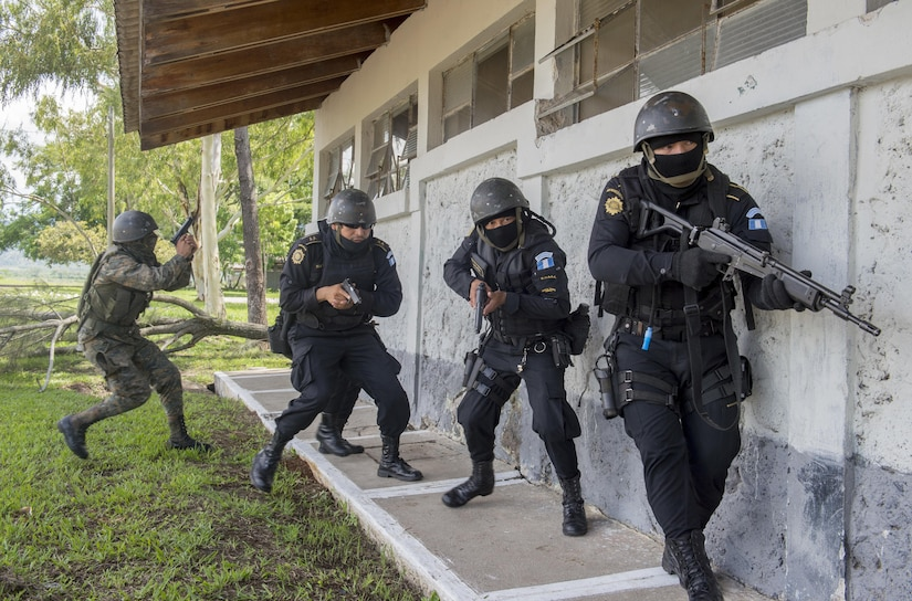 A joint team of Guatemalan police and soldiers stack up before entering a building during a evaluation exercise at Jupiata, Guatemalan, 16 June 2016. Approximately 40 U.S. Army Soldiers are deployed to Jupiata to provide training to National Civil Police (Policia Nacional Civil) and Guatemalan Army (Ejercito Nacional de Guatemala) members in order to better prepare them to combat illegal drug trafficking operations across the country. (U.S. Air Force photo by Tech. Sgt. Trevor Tiernan)