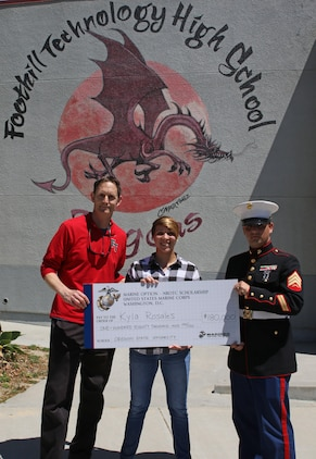 Foothill Technology High School Principal Joe Bova, and Sergeant Brian Robert, recruiter of Recruiting Sub Station Ventura, present a Naval Reserve Officers Training Corps Scholarship check to Kyla Rosales at Foothill Technology High School in Ventura, Calif., April 26, 2017. (U.S. Marine Corps photo by Staff Sgt. Alicia R. Leaders/Released)