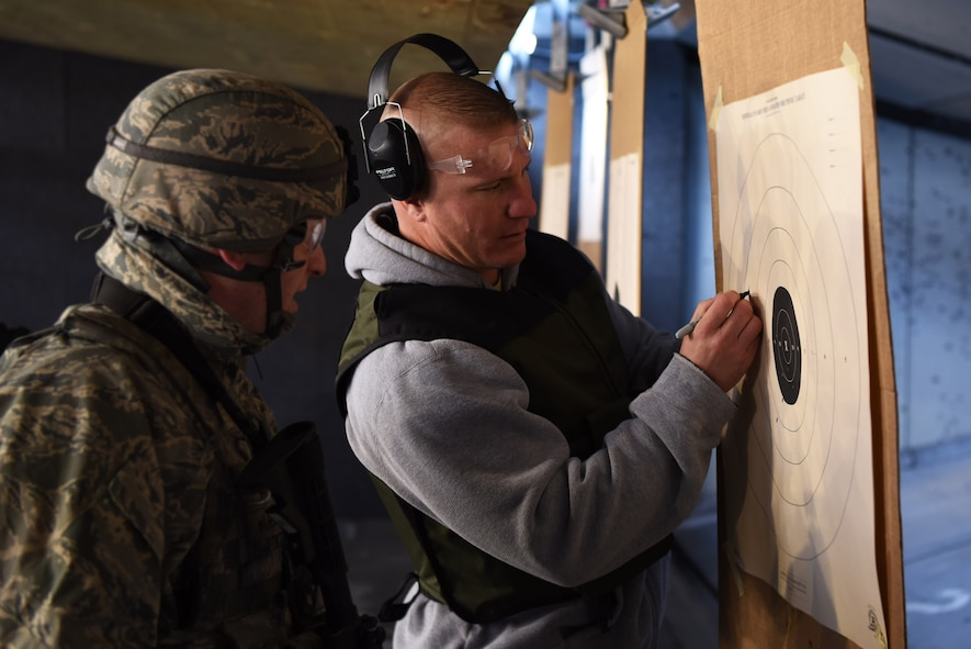 Jason Spillis, Adams County Sheriff Department detective and U.S. Air Force reservist, marks missed shots for Airman 1st Class Alexander Warren, 460th Security Forces Squadron member, as he zeroes in the sight on his rifle, Apr. 22, 2017, at the Flatrock Regional Training Center in Commerce City, Colo. After zeroing in their sights, each SFS member fired at their target while changing shooting positions, and while maneuvering tactically. (U.S. Air Force photo by Airman 1st Class Holden S. Faul/ Released)