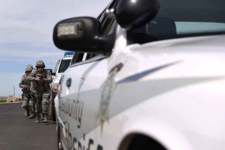 Senior Airman Rachel Kirk, 302nd Security Forces Squadron member, leads members of the 460th Security Forces Squadron Emergency Services Team as they approach a suspect's vehicle during a training exercise Apr. 23, 2017, at the Flatrock Regional Training Center in Commerce City, Colo. Due to the 302nd SFS already having an EST, a few members decided to take the opportunity to join Team Buckley and to enhance their tactical skillsets.  (U.S. Air Force photo by Airman 1st Class Holden S. Faul/ Released)