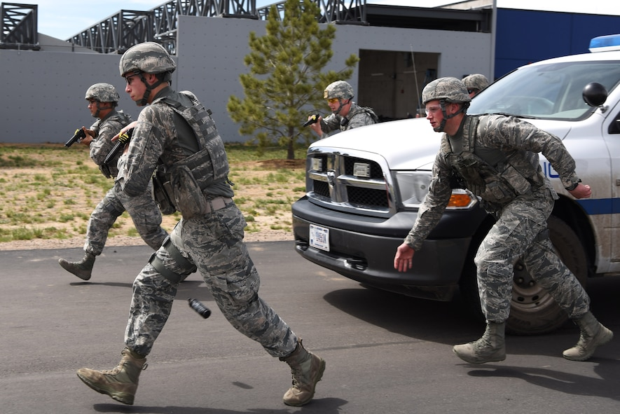 Members of the 460th Security Forces Squadron Emergency Services Team run towards a stopped vehicle prior to apprehending the suspect during a training event Apr. 23, 2017, at the Flatrock Regional Training Center in Commerce City, Colo. Adams County Sheriff Department Special Weapons and Tactics team members worked with the EST to help them learn the process of quickly, safely and effectively approaching a vehicle. (U.S. Air Force photo by Airman 1st Class Holden S. Faul/ Released)