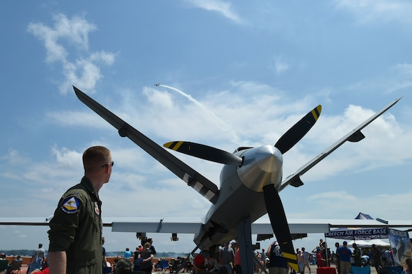 An Airman assigned to the 432nd Wing/432nd Air Expeditionary Wing watches one of the air demonstrations performed during the 2017 Gulf Coast Salute Open House and Airshow April 22, 2017, at Tyndall Air Force Base, Fla. Airmen from Creech Air Force Base, Nev., debuted the model at the air show and were able to communicate the MQ-9's capability and mission sets to visitors. (U.S. Air Force photo/Airman 1st Class James Thompson)