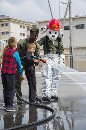 U.S. Marine Corps Lance Cpl. Akeem Mcfarlane, aircraft rescue firefighter with Headquarters & Headquarters Squadron teaches Gabriel Keller, a Junior Recruit Day participant, how to use a fire hose during the Aircraft Rescue and Firefighter training portion of Marine Aircraft Group 12's Junior Recruit Day at Marine Corps Air Station Iwakuni, Japan, April 21, 2017. The purpose of Junior Recruit Day is to increase family readiness in the community by showing children and young adults what their parents do on a daily basis. (U.S. Marine Corps photo by Mason Roy)