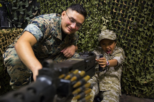 U.S. Marine Corps Cpl. Jeffery Aceti, left, a combat engineer with Marine Wing Support Squadron (MWSS) 171, assists Cosme Rosete, a Junior Recruit Day participant, with the Indoor Simulated Marksmanship Trainer's M2 .50 caliber heavy-machine gun during Marine Aircraft Group 12's Junior Recruit Day at Marine Corps Air Station Iwakuni, Japan, April 21, 2017. The purpose of Junior Recruit Day is to increase family readiness in the community by showing children and young adults what their parents do on a daily basis. (U.S. Marine Corps photo by Pfc. Mason Roy)