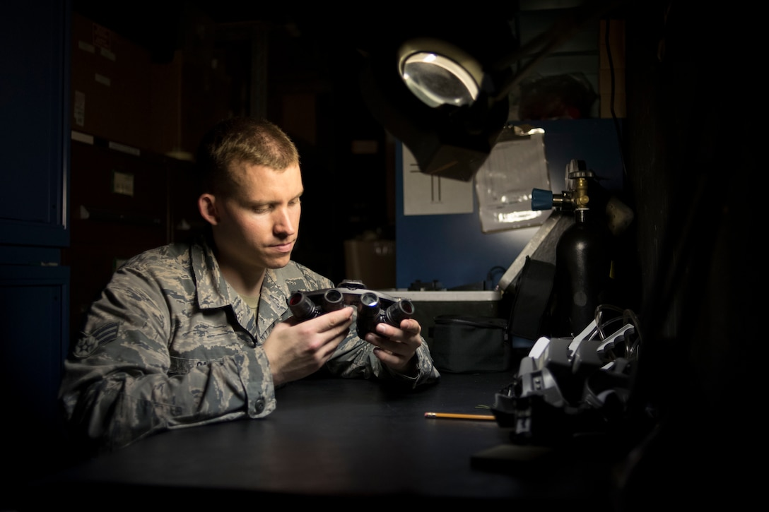 Senior Airman Joseph Gago, an 18th Operations Support Squadron aircrew flight equipment technician assigned to the 44th Fighter Squadron, inspects night vision goggles April 18, 2017, at Kadena Air Base, Japan. Aircrew flight equipment Airmen work day and night to inspect, repair and modify helmets, night vision goggles, life rafts and chemical gear to keep aircrews safe and able to complete the mission at hand. (U.S. Air Force photo/ Senior Airman John Linzmeier)