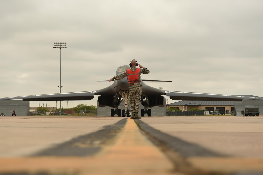 Airman 1st Class Chance Barfield, a 7th Aircraft Maintenance Squadron crew chief, marshals Maj. Gen. Thomas Bussiere, the 8th Air Force commander, toward the runway for his B-1B Lancer familiarization flight at Dyess Air Force Base, Texas, April 19, 2017. During his visit, Bussiere was given the opportunity to fly in the B-1 to understand the bomber's critical role in security and deterrence while at home and abroad. (U.S. Air Force photo/Airman 1st Class Emily Copeland)