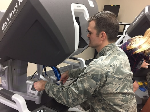 Maj. (Dr.) Toby Lees, urologist, Surgical Specialties Flight commander, 88th Medical Group, manipulates the da Vinci Xi surgical robotic system from one of its two consoles during the new system's unveiling at the Wright-Patterson Medical CenterApril 20.(Skywrighter photo/Amy Rollins)