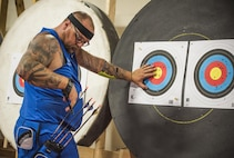 A Warrior CARE athlete, Ed Loves pulls his arrows from the target during an archery session at the adaptive sports camp at Eglin Air Force Base, Fla., April 26. The base hosts the week-long Wounded Warrior CARE event that helps recovering wounded, ill and injured military members through specific hand-on rehabilitative training. (U.S. Air Force photo/Ilka Cole)