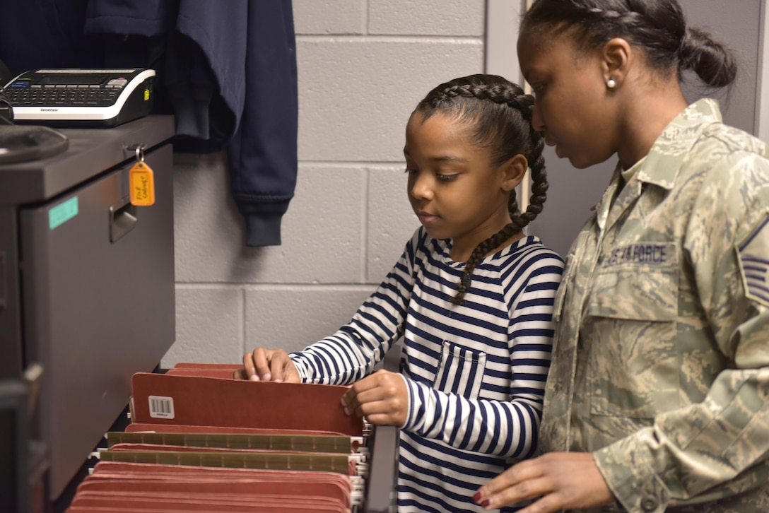 April is designated as the Month of the Military Child, underscoring the important role military children play in the armed forces community. The Month of the Military Child helps raise awareness about the unique struggles military children face, builds resiliency to help them cope with those challenges, and celebrates their sacrifices, which often go unrecognized. Master Sgt. Chastity Morgan, a knowledge operations specialist assigned to the 180th Fighter Wing, and her daughter file personnel mobilization folders at the wing, March 10, 2017 Air National Guard Photo by Tech. Sgt. Nic Kuetemeyer.