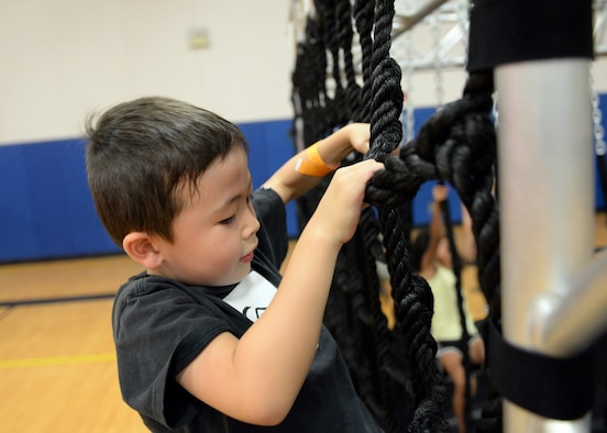 Diesel McManus, (age 5), climbed through the Alpha Warrior obstacle course during the Alpha Warrior team's visit April 26, 2017, at Luke Air Force Base, Ariz. The team came to visit Luke Airmen to help showcase the importance of fitness readiness and set up an obstacle course for the children of Luke to practice on. (U.S. Air Force photo by Airman 1st Class Heidi Goodsell)