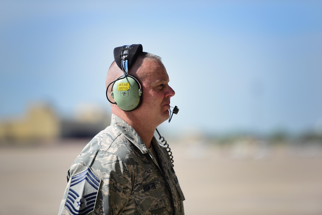 """U.S. Air Force Chief Master Sgt. Darron Hunter, the 509th Maintenance Group (MXG) superintendent, performs pre-flight checks on a B-2 Spirit and signals to the mission commander that he is clear and free to move to the runway at Whiteman Air Force Base, Mo., April 24, 2017. During Hunter's first assignment at Whiteman, he served as the dedicated crew chief (DCC) on the Spirit of Kitty Hawk, tail number 93-1086, from 2000 to 2002, before moving into Quality Assurance and Production for another seven years. In 2015, Hunter returned to the 509th as the MXG superintendent, bringing his career full circle before retiring. For one last farewell, Hunter once more performed the role of the DCC for his old aircraft, """"1086."""" (U.S. Air Force photo by Airman 1st Class Jazmin Smith)"""