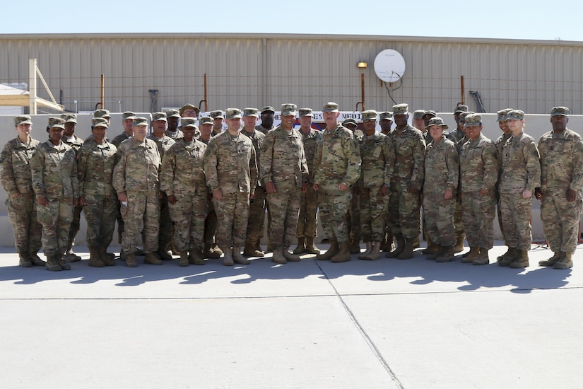Lt. Gen. Michael Garrett, commanding general of U.S. Army Central and Maj. Gen. William Lee, commanding general of 3rd medical Command stand with the Soldiers of the 3rd Medical Command (Deployment Support) stationed in Qatar to celebrate 25 years of partnership, April 21, at Camp As Sayliyah. The 3rd Medical Command painted a barrier providing a physical tribute to the partnership between the two commands. (U.S. Army photo by Sgt. Bethany Huff, USARCENT Public Affairs)