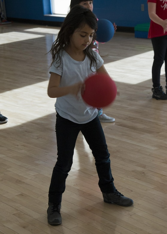 A Youth Center child exercises with a fitness ball during an event at the McAdoo Fitness Center at Minot Air Force Base, N.D., April 17, 2017. This group of second and third-graders participated in a mock fitness assessment, bounce house, a video exercise with fitness balls and wallyball. (U.S. Air Force photo/Airman 1st Class Alyssa M. Akers)