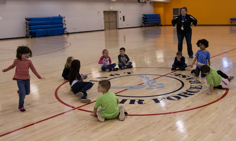 Youth Center children play duck duck goose during an event at the McAdoo Fitness Center at Minot Air Force Base, N.D., April 17, 2017. This group of kindergarteners and first-graders participated in a mock fitness assessment, bounce house, a video exercise with fitness balls and group games. (U.S. Air Force photo/Airman 1st Class Alyssa M. Akers)