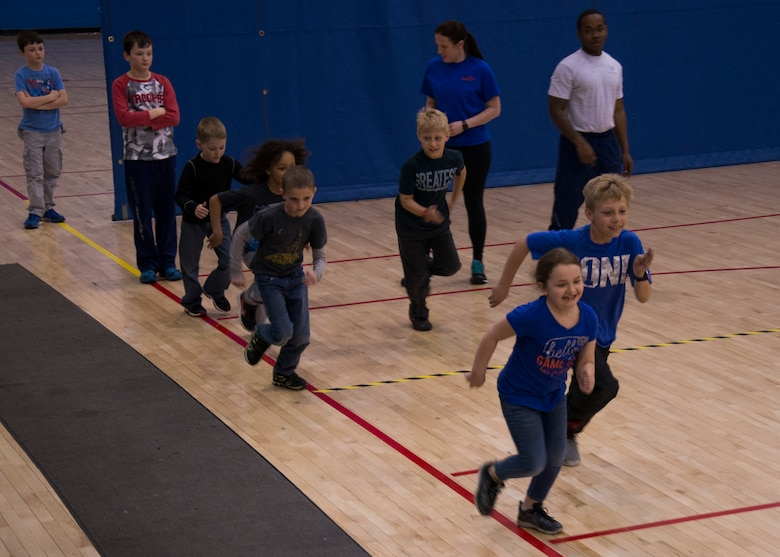 Youth Center children begin the run portion of a mock fitness assessment during an event at the McAdoo Fitness Center at Minot Air Force Base, N.D., April 17, 2017. The mock fitness assessment consisted of one minute of both pushups and situps as well as running a few laps around basketball courts. (U.S. Air Force photo/Airman 1st Class Alyssa M. Akers)