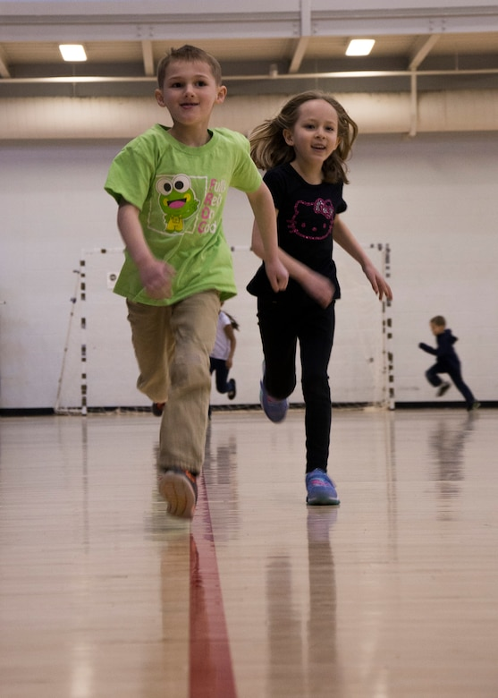 Youth Center children race around basketball courts during a mock fitness assessment at the McAdoo Fitness Center at Minot Air Force Base, N.D., April 17, 2017. The fitness center hosted the event for the children to promote a healthy lifestyle in school-age children. (U.S. Air Force photo/Airman 1st Class Alyssa M. Akers)