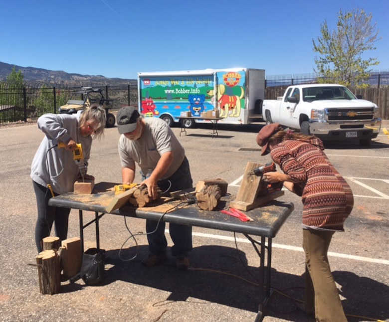 ABIQUIU LAKE, N.M. – Volunteers work on building housing for pollinators during the Pollinator Party at the lake, April 22, 2017. Sixteen volunteers total built housing for pollinators by drilling 3-inch deep, ¼-inch holes in old lumber and brush, putting on a roof and attaching it to a wall or post.