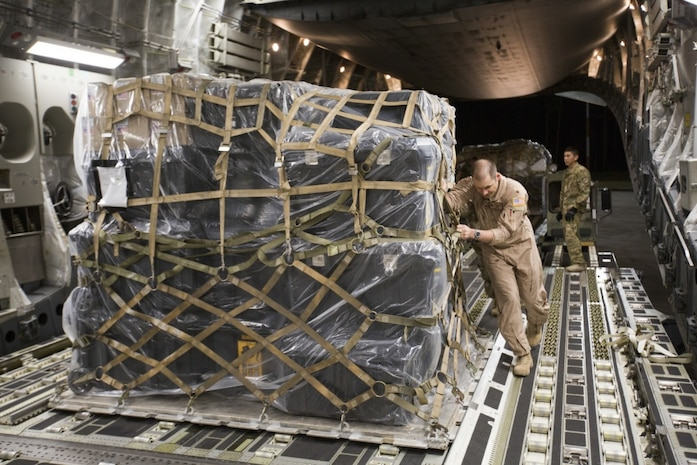 MARINE CORPS AIR STATION CHERRY POINT, N.C. – U.S. Air Force Maj. Robert Riggs, U.S. Marine Corps Forces, Special Operations Command air mobility liaison officer (AMLO), assists in loading cargo aboard a C-17 aircraft at MCAS Cherry Point. As MARSOC's AMLO, Riggs provides a critical link of communication between the airlift and ground forces in the area of operations. He facilitated the mission from planning and coordination through hands-on facilitation by piloting the aircraft as it deployed and re-deployed two MARSOC units. (U.S. Marine Corps photo by Sgt. Salvador Moreno, released)