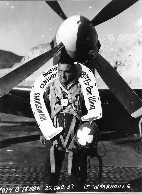 "Ernie poses with his ""lucky horseshoe"" following his 100th mission in Korea.  Helmet is blue with white four-leaf clover."
