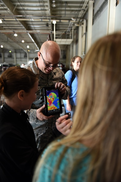 Staff Sgt. Robert Kedrowski, 312th Training Squadron course development specialist, shows thermal technology to children during the Childs Tour at the Louis F. Garland Department of Defense Fire Academy on Goodfellow Air Force Base, Texas, April 28, 2017. Kedrowski showed them that certain objects may make our hands colder and explained the uses of thermal technology. (U.S. Air Force Caelynn Ferguson/ Released)