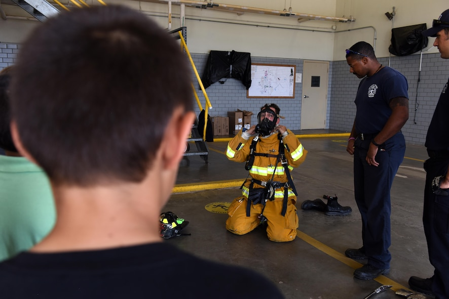 A child watches fire protection professionals demonstrate how to put on bunker gear at the Goodfellow fire department on Goodfellow Air Force Base, Texas, April 28, 2017. The fire protection professionals also taught them about the necessity of motion sensors and air tanks. (U.S. Air Force photo by Airman 1st Class Caelynn Ferguson/ Released)