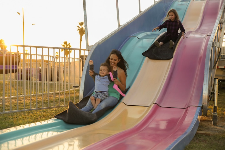 Annie Smack, wife of Gunnery Sgt. Eric Smack, battery gunnery sergeant, 3rd Battalion, 11th Marine Regiment, slides down a giant slide with her son, Carter, 1, during the Earth Day Extravaganza at Lincoln Military Housing Athletic Field aboard Marine Corps Air Ground Combat Center, Twentynine Palms, Calif., April 21, 2017. LMH and Natural Resources and Environmental Affairs hosted the event to make Combat Center patrons more conscious about the environment in a fun and informative way. (U.S. Marine Corps photo by Lance Cpl. Dave Flores)