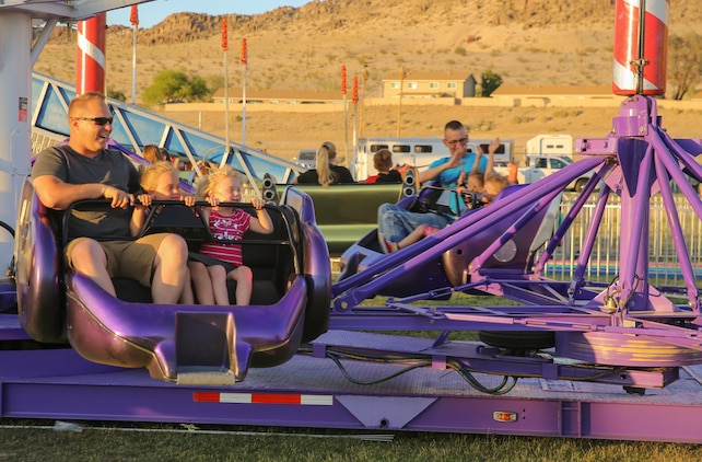 Sgt. Aaron Medlin, squad leader, 3rd Battalion, 4th Marines, 7th Regiment, enjoys a carnival ride with his daughters during the Earth Day Extravaganza at Lincoln Military Housing Athletic Field at Marine Corps Air Ground Combat Center, Twentynine Palms, Calif., April 21, 2017. LMH and Natural Resources and Environmental Affairs hosed the event to encourage Combat Center residents to be more aware of the environment. (U.S. Marine Corps photo by Lance Cpl. Dave Flores)