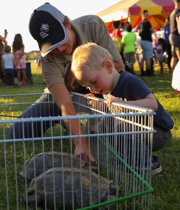 Mary Lane Poe, biologist, Natural Resource and Environmental Affairs, shows a Combat Center child the different parts of a desert tortoise using Thelma and Louise, desert tortoise ambassadors,  as a reference during the Earth Day Extravaganza at the Lincoln Military Athletic Field at Marine Corps Air Ground Combat Center, Twentynine Palms, Calif, April 21, 2017. LMH and Natural Resources and Environmental Affairs hosted the event to encourage Combat Center residents to be more aware of the environment. (U.S. Marine Corps photo by Lance Cpl. Christian Lopez)