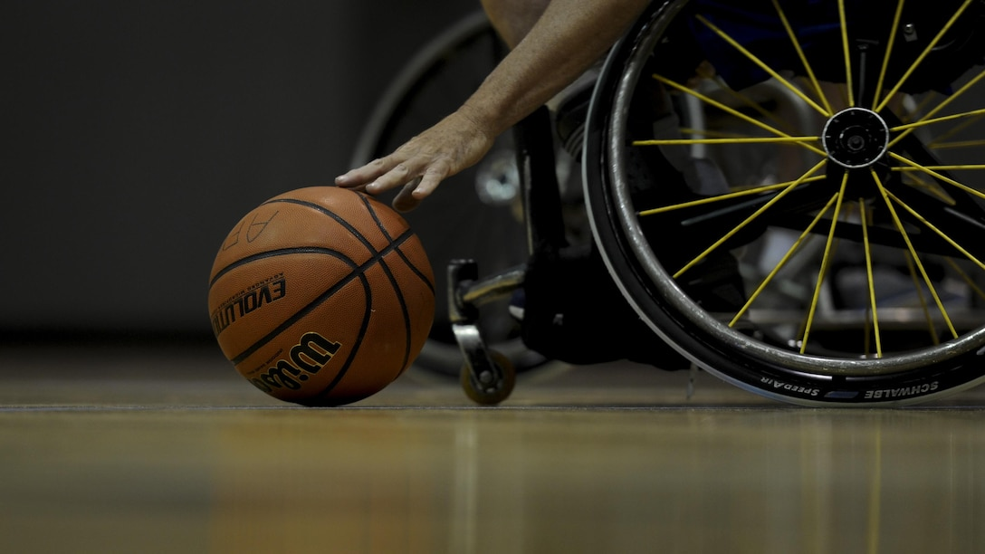 Jerry Terry, the assistant coach of the Air Force wheelchair basketball team, picks up a basketball during practice at Hurlburt Field, Fla., April 24, 2017. This Terry's first year coaching with the team. (U.S. Air Force photo by Airman 1st Class Dennis Spain)