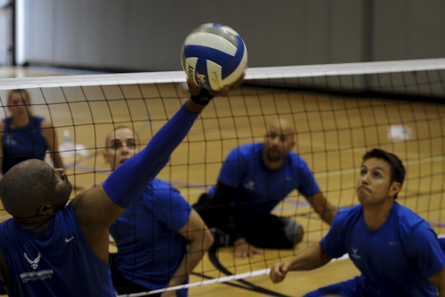 Larry O'Neil, a member of the Air Force sitting volleyball team, reaches back to set the volleyball at Hurlburt Field, Fla., April 24, 2017. Players participated in a variety of drills and a scrimmage game. (U.S. Air Force photo by Airman 1st Class Dennis Spain)