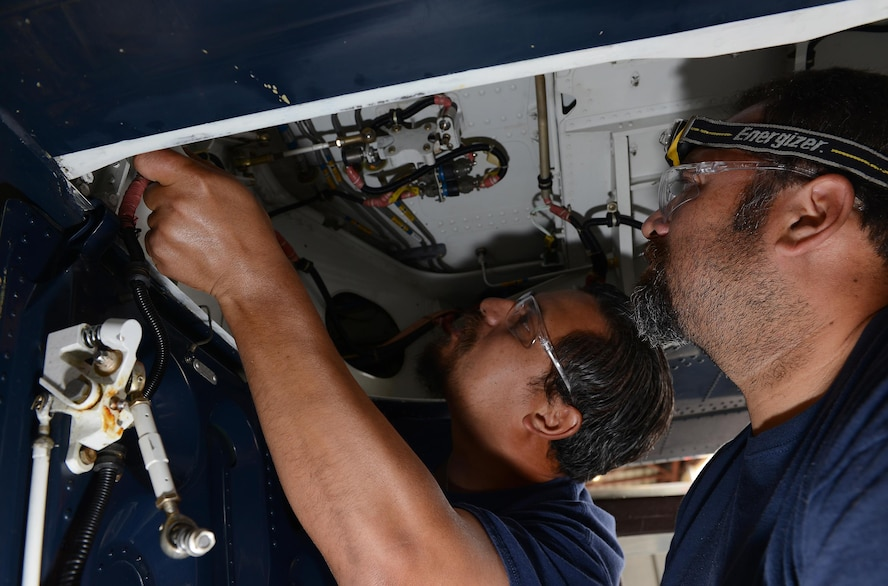 "Leo Gonzalez (left) and Armando Patiño (right), 47th Maintenance Directorate maintainers, inspect the landing gear of a T-6 Texan II on Laughlin Air Force Base, Texas, April 12, 2017. Laughlin has the lowest amount of T-6 hangar queens in Air Education and Training Command. A ""hangar queen"" is an aircraft that hasn't been flown in more than 30 days. (U.S. Air Force photo/Airman 1st Class Benjamin N. Valmoja)"