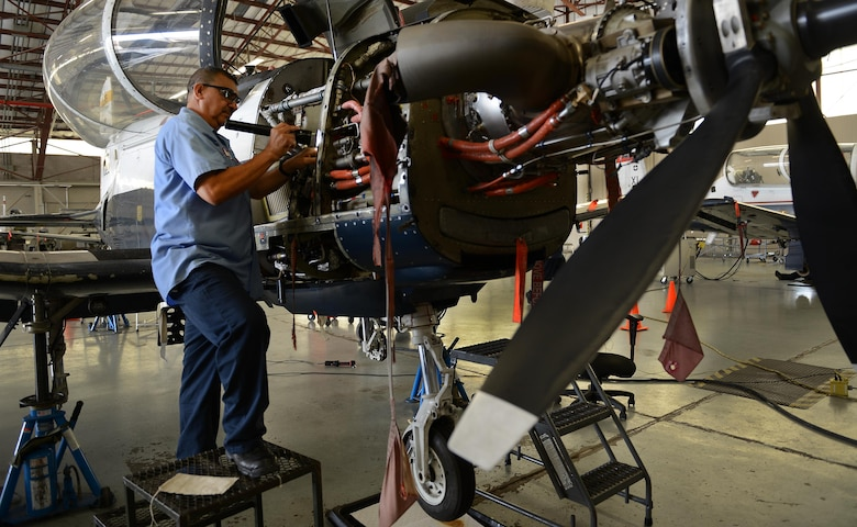 "Raul Castaneda, 47th Maintenance Directorate maintainer, inspects the engine bay of a T-6 Texas II on Laughlin Air Force Base, Texas, April 12, 2017. Castaneda is part of the maintenance crew that restored Laughlin's hangar queens, putting Laughlin at the top of Air Education and Training Command with the least amount of T-6 hangar queens. A ""hangar queen"" is an aircraft that hasn't been flown in more than 30 days. (U.S. Air Force photo/Airman 1st Class Benjamin N. Valmoja)"