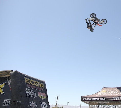 Cal Vallone, professional freestyle motocross rider, performs a trick during the Provost Marshal's Office annual Community Safety Event at Victory Field aboard Marine Corps Air Ground Combat Center, Twentynine Palms, Calif., April 21, 2017. PMO hosted the event to educate the community on various programs and strengthen community based partnerships. (U.S. Marine photo by Lance Cpl. Natalia Cuevas)