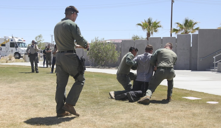 Special Reaction Team members, Provost Marshals Office, subdue Agent Cody Cunningham, criminal investigator, Criminal Investigations Division, with an X26P Taser during PMO's annual Community Safety Event at Victory Field aboard Marine Corps Air Ground Combat Center, Twentynine Palms, Calif., April 21, 2017. PMO hosted the event to educate the community on various programs and strengthen community based partnerships. (U.S. Marine photo by Lance Cpl. Natalia Cuevas)