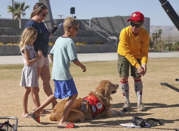 Laura Finlon, Joshua Tree Search and Rescue team member, introduces Gunner, comfort dog, to Combat Center patrons during the Provost Marshal's Office annual Community Safety Event at Victory Field aboard Marine Corps Air Ground Combat Center, Twentynine Palms, Calif., April 21, 2017. PMO hosted the event to educate the community on various programs and strengthen community based partnerships. (U.S. Marine photo by Lance Cpl. Natalia Cuevas)