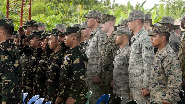 Philippine Soldiers and U.S. military engineers stand for the Philippine national anthem during a groundbreaking ceremony for Balikatan 2017 in Ormoc City, Leyte. Leaders from the Armed Forces of the Philippines, U.S. military, and Ormoc City gathered to commemorate the beginning of engineering projects for new classrooms at Margen Elementary School in Ormoc City, April 25, 2017. Balikatan is an annual U.S.-Philippine military bilateral exercise focused on a variety of missions, including humanitarian assistance and disaster relief and counterterrorism.