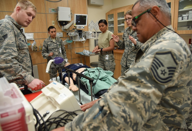 "Members of the 81st Medical Operations Squadron simulate administering shock treatment to a ""patient"" during Code Blue Thursday in the Keesler Medical Center emergency room April 27, 2017, on Keesler Air Force Base, Miss. Emergency Room staff members coordinated with the simulation lab to use human patient simulators for running various advanced cardiac life support scenarios to improve Keesler's new medical technicians' skills and get them familiar with emergency equipment. (U.S. Air Force photo by Kemberly Groue)"