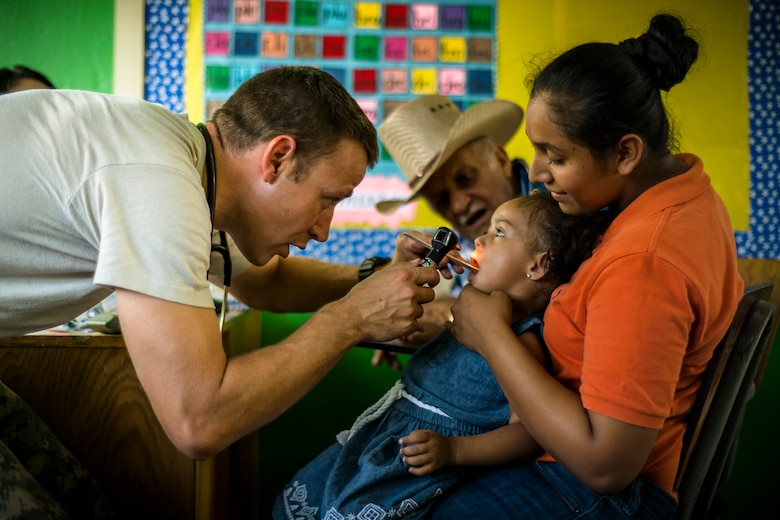 U.S. Army Capt. Adam West checks the throat of a Honduran child at a Military Partnership Engagement in Santa Rosa de Aguan, Colon, Honduras, Apr. 22, 2017. Joint Task Force – Bravo Medical Element, provided care to more than 850 patients during a Medical Readiness Training Exercise in Cooperativa village, Colon, Honduras, Apr. 20-21, 2017. MEDEL also supported a Military Partnership Engagement and assisted more than 650 patients with the Hondurian Navy in Santa Rosa de Aguan, Colon, Honduras, Apr. 22, 2017. (U.S. Air National Guard photo by Master Sgt. Scott Thompson/released)