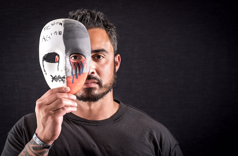 Retired Air Force Tech. Sgt. Chris Ferrell, a former explosive ordnance disposal technician who suffers from post-traumatic stress disorder and traumatic brain injury after combat tours in Afghanistan and Iraq, displays a mask he painted in Hanover, Pa., April 5, 2017. The mask, which bears the initials and dates of death of his teammates, Air Force Tech. Sgts. Tony Campbell and Adam Ginett, is a form of art therapy employed by therapists to help PTSD patients verbalize past traumatic events. It is one of the therapies that will be used at the Air Force's Invisible Wounds clinic scheduled to open at Eglin Air Force Base, Fla., in 2018. Air Force photo by J.M. Eddins Jr.