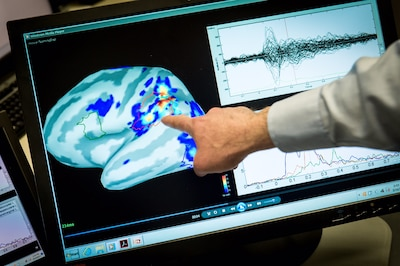 Magnetoencephalography laboratory scientist Mihai Popescu points out areas of magnetic activity in a brain on a display at the National Intrepid Center of Excellence at Walter Reed National Military Medical Center in Bethesda, Md., March 16, 2017. Air Force photo by J.M. Eddins Jr.