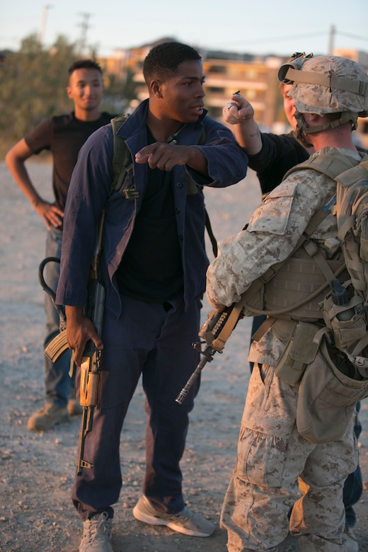 Cpl. Brandon Armwood, roleplayer, Tactical Training Exercise Control Group, interacts with a Marine from 2nd Battalion, 6th Marine Regiment during a non-combatant Evacuation Operation exercise as part of Weapons and Tactics Instructor Course 2-17 aboard Marine Corps Air Ground Combat Center Twentynine Palms, Calif., April 21, 2017. NEO exercises simulate real-life scenarios where non-combatants are evacuated from a potentially hostile area. (U.S. Marine Corps photo by Cpl. Julio McGraw)